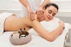 Male masseur doing professional body massage. Hands massaging female back and shoulders. Professional body treatment or relaxation procedure at spa salon. Health Royalty Free Stock Photo