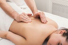 Closeup of hands massaging female shoulders and back Royalty Free Stock Photo