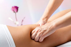 Hands massaging female back thigh. Stock Photo