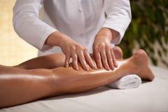 Hands massaging female calf Royalty Free Stock Image