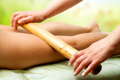 Hands massaging female legs with bamboo. Royalty Free Stock Images