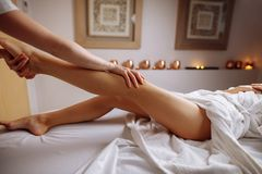 Hands massaging human calf muscle.Therapist applying pressure on leg. Hands massaging human calf muscle.Therapist applying pressure on female leg Royalty Free Stock Photos