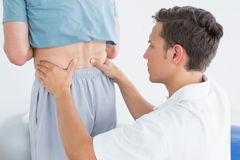 Hands massaging mans lower back in gym hospital. Closeup of hands massaging mans lower back in the gym at hospital Stock Image