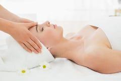 Hands massaging woman's face at beauty spa Stock Photos