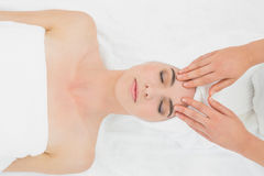 Hands massaging a woman's forehead at beauty spa Stock Images