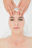 Hands massaging woman's forehead at beauty spa Royalty Free Stock Photos