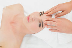 Hands massaging woman's forehead at beauty spa Stock Photo