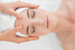 Hands massaging woman's forehead at beauty spa Royalty Free Stock Photo