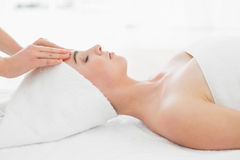 Hands massaging woman's forehead at beauty spa Stock Image