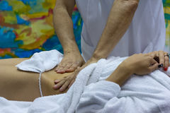 Hands of the masseur and the client`s body during massage treatm Stock Photos
