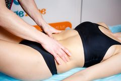 The hands of a masseur make a relaxing massage to a woman on the abdominal abdomen for toning the muscles. Close-up stock images