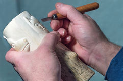 Hands of a master crafts wooden handle chisel. Royalty Free Stock Photos