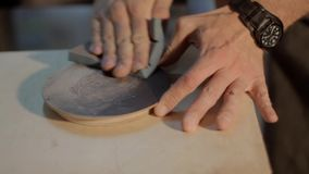 Hands of the master grind a round wooden product