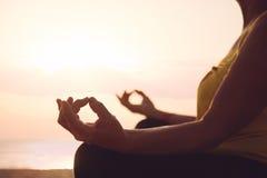 Hands of mature woman practicing yoga. At lotus pose, at the sea beach Royalty Free Stock Photo