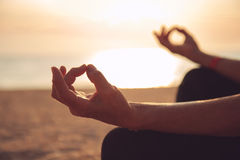 Hands of mature woman practicing yoga. At lotus pose, at the sea beach Stock Photography