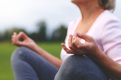 Hands of mature woman practicing yoga. At lotus pose, outdoors Royalty Free Stock Photo