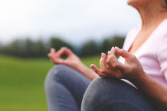Hands of mature woman practicing yoga. At lotus pose, outdoors Stock Image