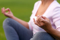 Hands of mature woman practicing yoga. At lotus pose, outdoors Royalty Free Stock Images