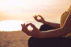 Hands of mature woman practicing yoga. At lotus pose, at the sea beach Stock Photo
