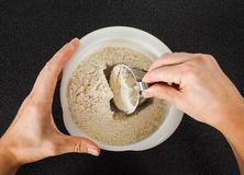 Hands measuring wheat flour from a bowl Stock Photography
