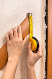 Hands measuring width of platband with tape measure Stock Photography