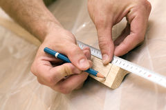 Hands measuring wood. Hands using a measuring tape and a pencil to measure wood on protective nylon covering for a DIY home improvement project royalty free stock image
