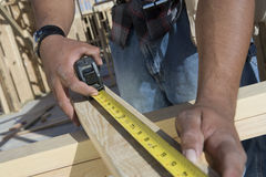 Hands Measuring Wooden Beam Stock Image