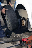 Hands of mechanic changing car wheel in auto repair service Stock Photos