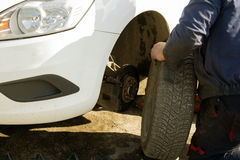 Hands of mechanic changing car wheel in auto repair service Stock Photo