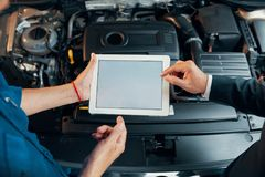 Car diagnostics. Hands of mechanic and customer using application on tablet computer when performing car diagnostic test royalty free stock photos
