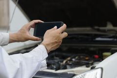 Hands of mechanic man taking a picture with mobile smart phone against car in open hood at the repair garage. royalty free stock photo