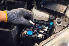 The hands of the mechanic replacing fuse in car and selects the correct fuse at garage .service and maintenance concept . Selective focus royalty free stock images