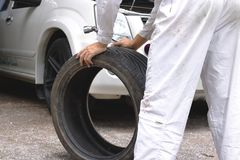 Hands of mechanic in white uniform holding tire at the repair garage background. Car service concept. Stock Photography