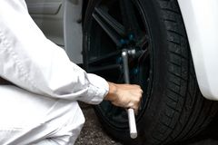 Hands of mechanic in white uniform holding wrench at the repair garage background. Car service concept. Hands of mechanic in white uniform holding wrench at the Royalty Free Stock Image