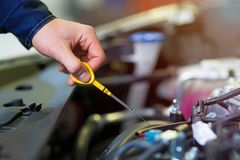 Mechanic checking engine oil in auto repair shop stock images