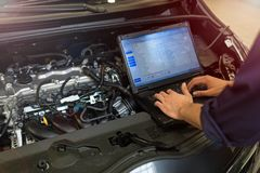 Mechanic Using Laptop While Examining Car Engine. Hands of mechanic working on car engine in auto repair shop royalty free stock photos