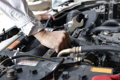 Hands of mechanic with wrench repairing engine of motor car under car hood. Royalty Free Stock Photography