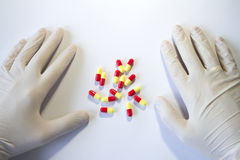 Hands in medical rubber gloves and red and yellow capsules. In the center Royalty Free Stock Image