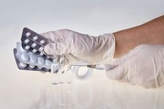 Hands of the medical worker in white gloves holding a syringe and tablets royalty free stock photo
