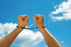 The hands of the men chained in handcuffs, on a background of the blue sky Royalty Free Stock Photography