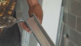 Hands of men cutting frame for mount drywall in unfinished apartments. Close-up stock footage