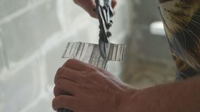 Hands of men cutting frame for mount drywall in unfinished apartments. Close-up stock video