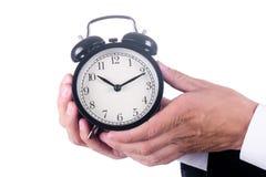 Hands of men holding alarm clock stock photo