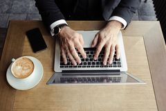 Hands men lie on the laptop, near a phone and cappuccino royalty free stock image
