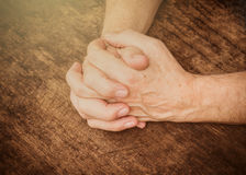 Hands of men praying on open wooden book Stock Images