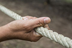 Hands of men ropes. Hands of men with ropes to help pull rope Stock Image