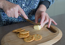 Hands of Middle-aged Woman Cutting Cheese. Stock Photo