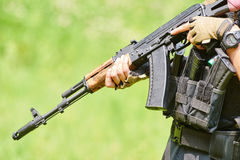Hands of military soldier with assault rifle. And camo suit outdoors Stock Photos