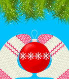 Hands in mittens hang on the Christmas tree ball. Stock Images