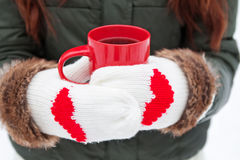 Hands in mittens with hearts holding cup Royalty Free Stock Photo